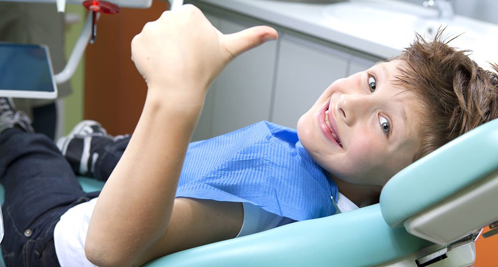 Happy child in dentist chair at Larkham House
