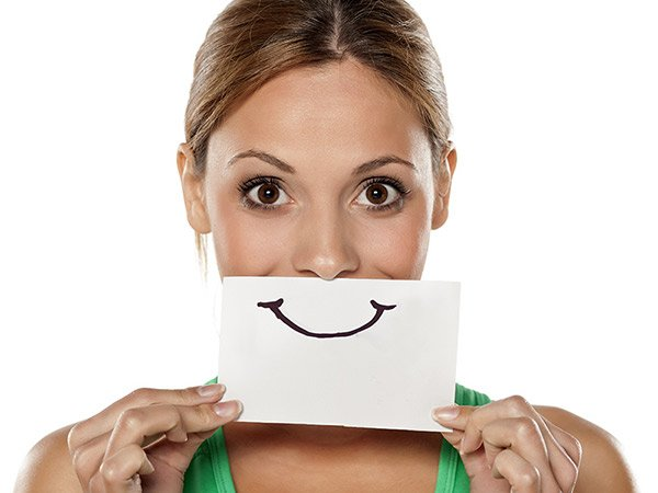 Smile drawing held over mouth